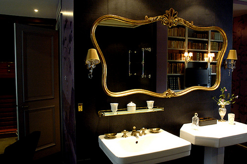 black bathroom with gold mirror frame