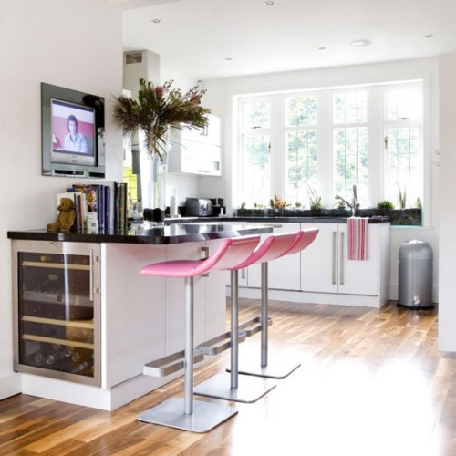white kitchen with pink stools