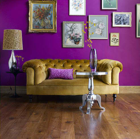 purple wall in living room with velvet chesterfield sofa and many decorating frames