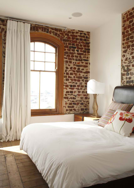 bedroom with old raw brick walls