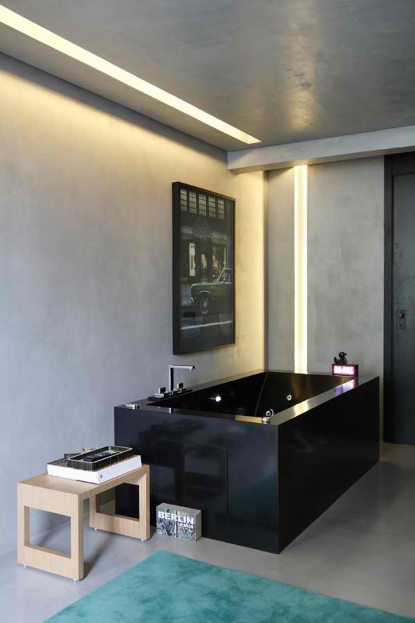 concrete batroom with black bathtub