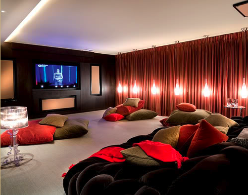 large home theater room with red curtains and hanging lights