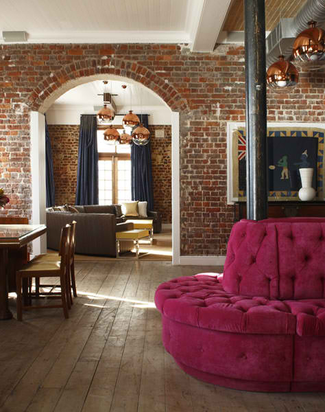 living room with old raw brick walls and fuchsia sofa