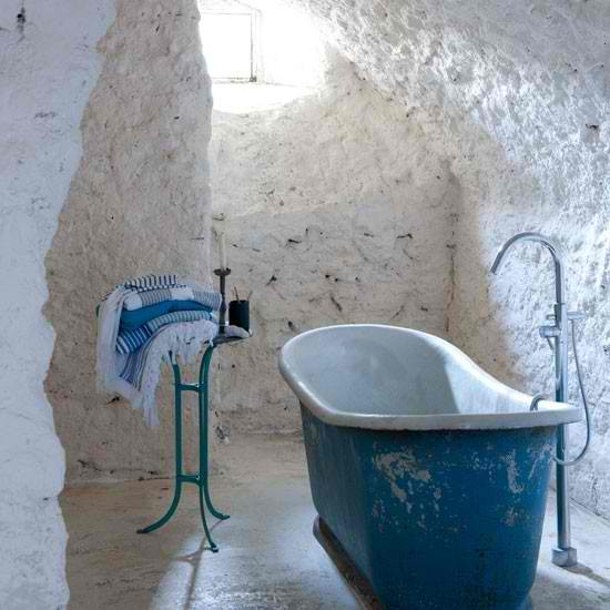 white stone bathroom with free standing bathtub