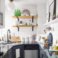 tiny grey kitchen with white tiles and wood open shelves
