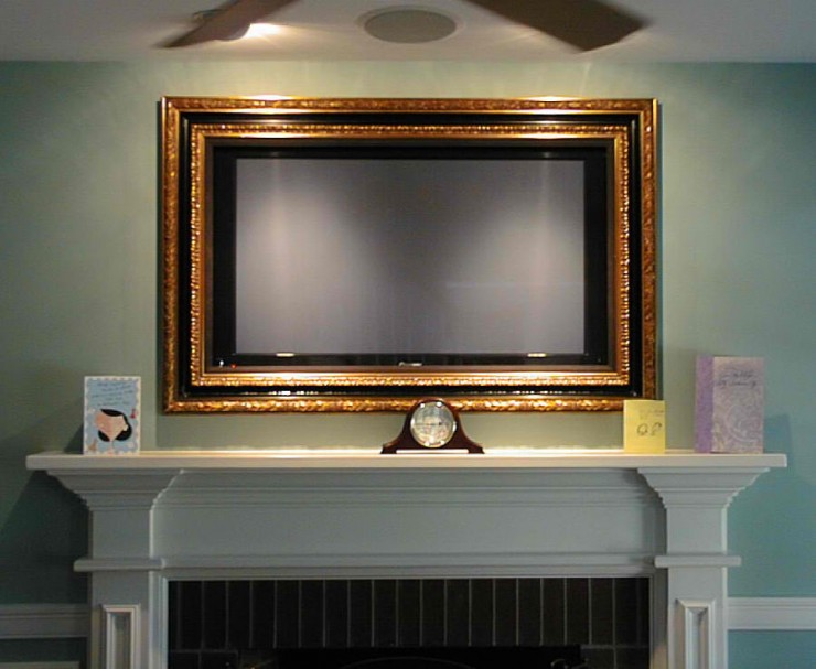 gold framed tv above fireplace