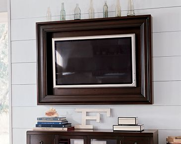 wood framed tv above fireplace