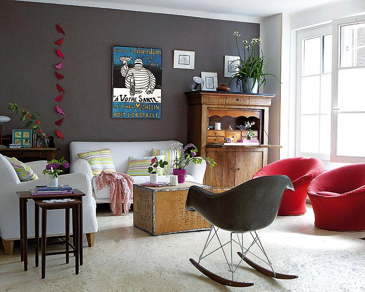 The dark color of the wall highlights the antique furniture.