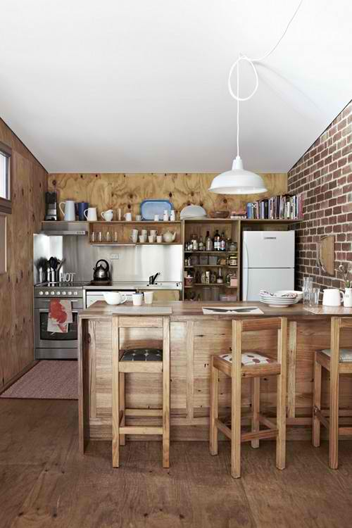red exposed brick wall in wood and steel kitchen