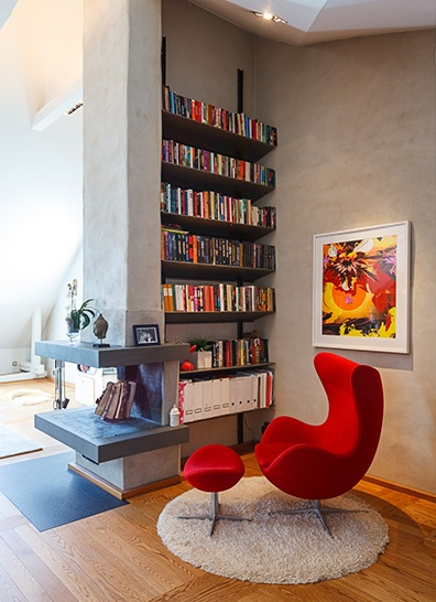 floating shelves and a red armchair