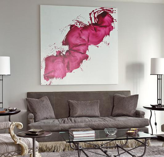 a gray sofa with a special painting above it