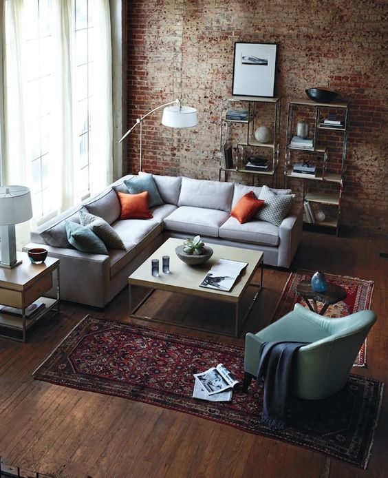light gray sofa with orange pillows