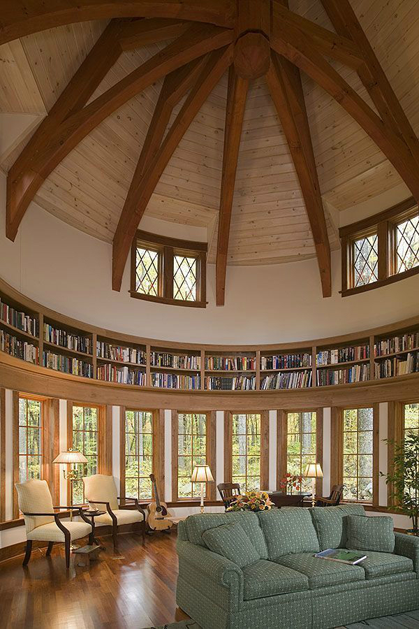 high ceiling with wood beams and a circular bookcase a