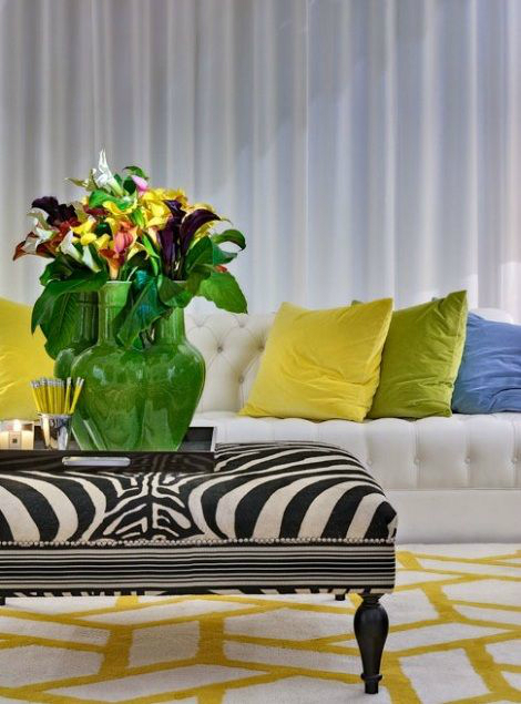 white living room with yellow blue and green pillows