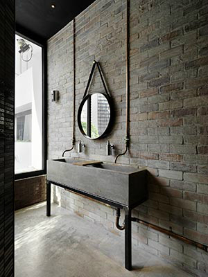 round mirror in industrial bathroom