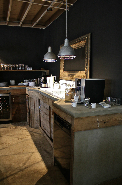 rustic industrial kitchen with black walls concrete counters
