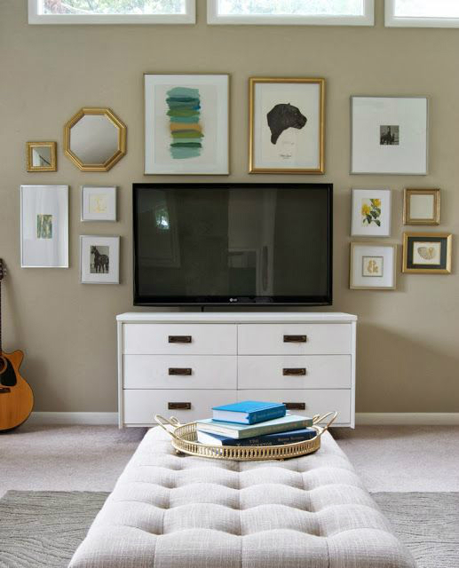 big TV on a drawer and light brown wall