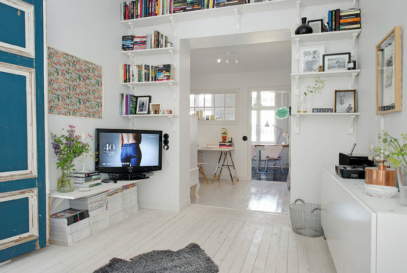 white living room with a TV on the corner