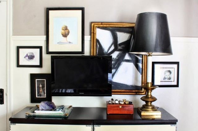 small TV with decorative frames in the background