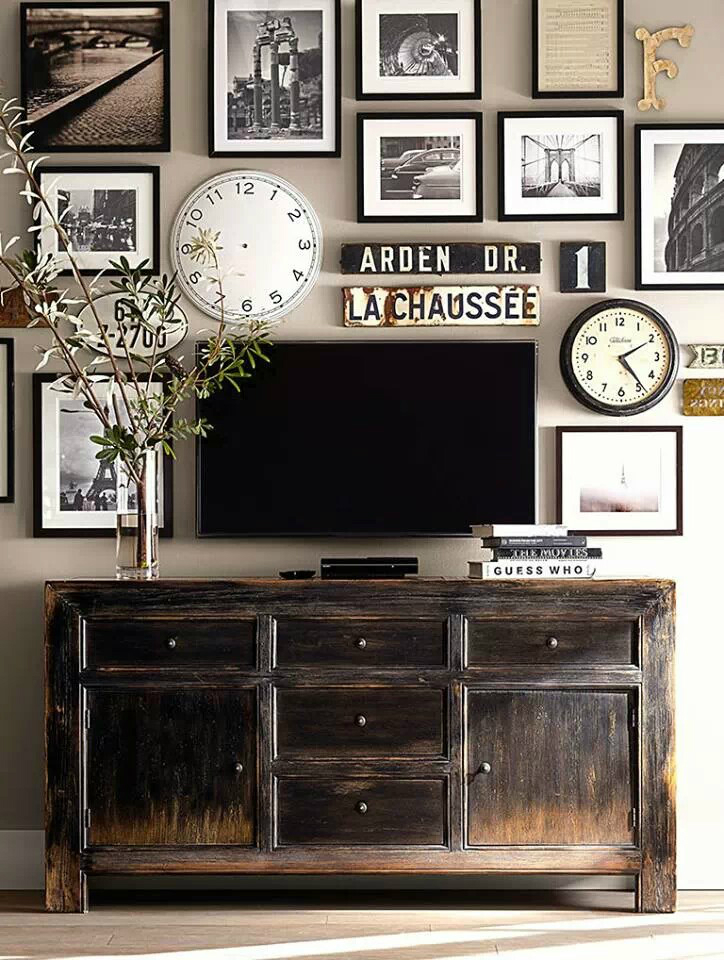 clocks and frames near TV and some vintage furniture