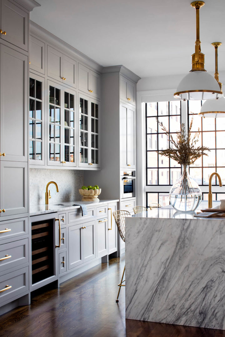 Floor to ceiling gray kitchen  with gold hardware