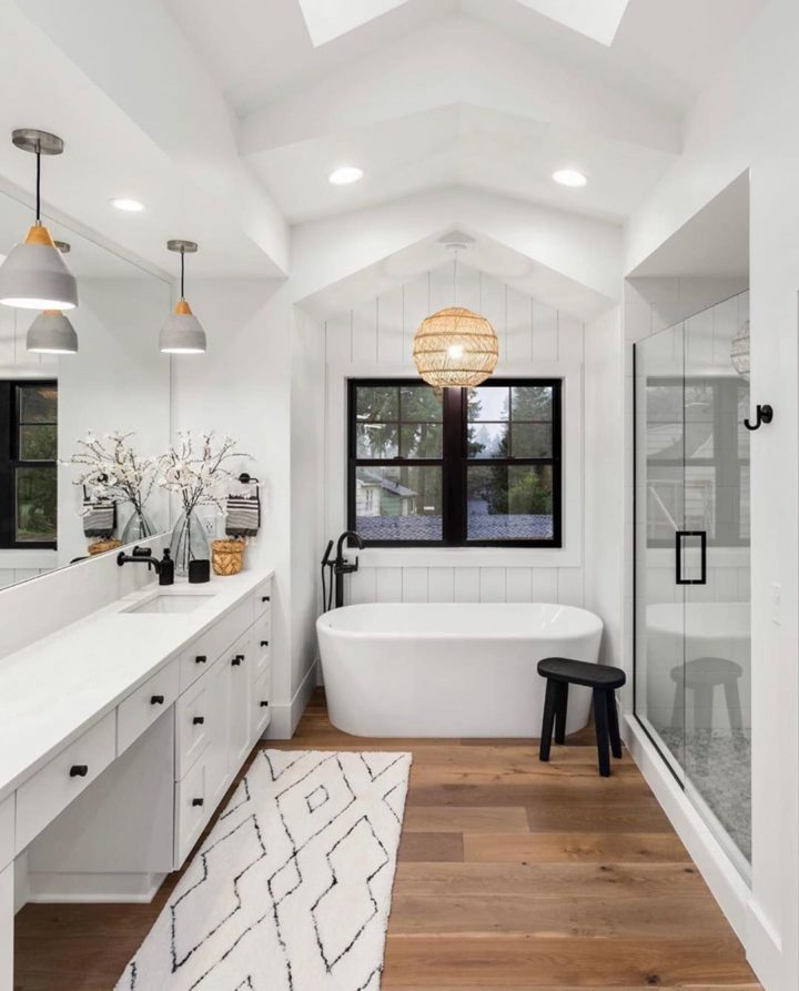 stylish white bathroom with wood floor tub and walk in shower