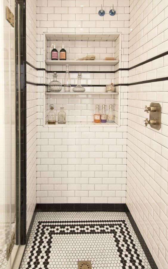 black and white walk in-shower with built-in wall shelving and grey tile grout