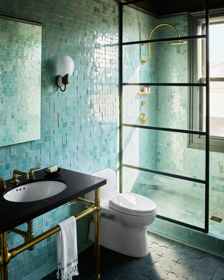 green and black walk in shower with hand-cut tiles and gold fixtures