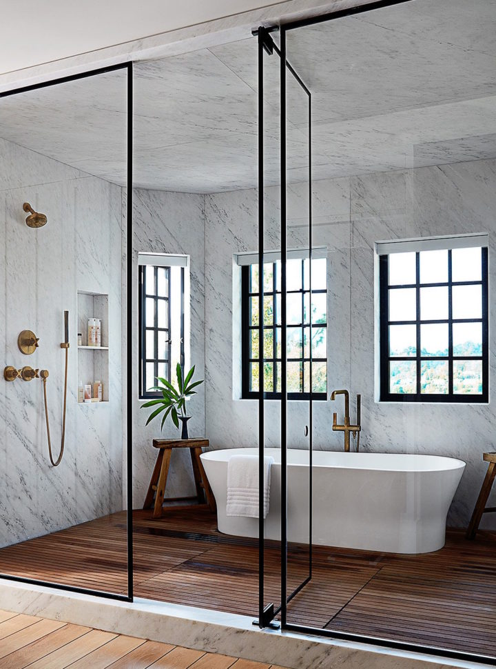 A steel-framed glass door encloses the master suite's shower and tub