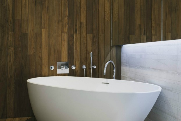 contemporary bathroom with wood wall and freestanding tub