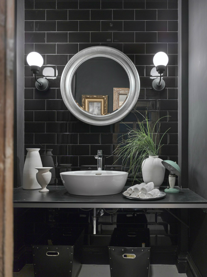 modern black bathroom with silver round mirror