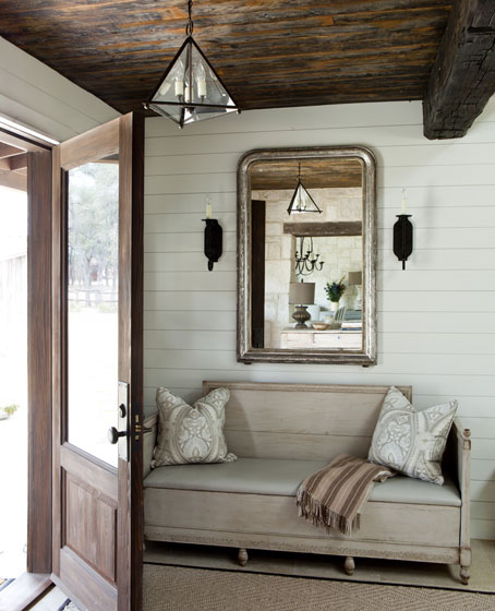 stylish traditional entrance with bench and mirror