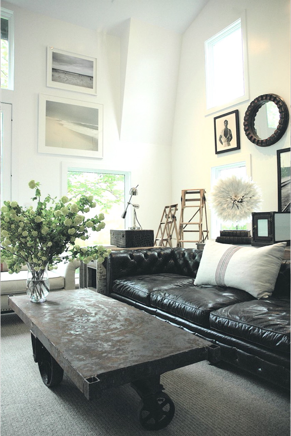 industrial style living room with black leather sofa and wal art