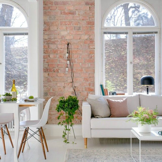 living room with brick wall high windows and white neutral and light colored furnishings