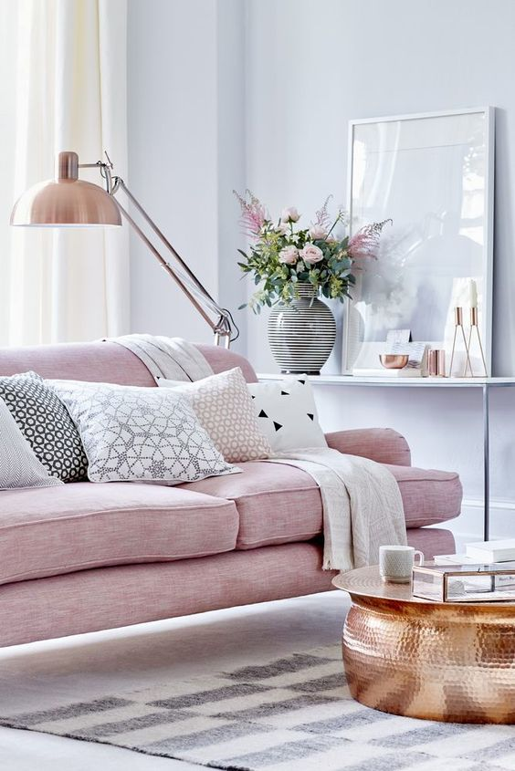 Feminine romantic living room with soft pink sofa and copper accents
