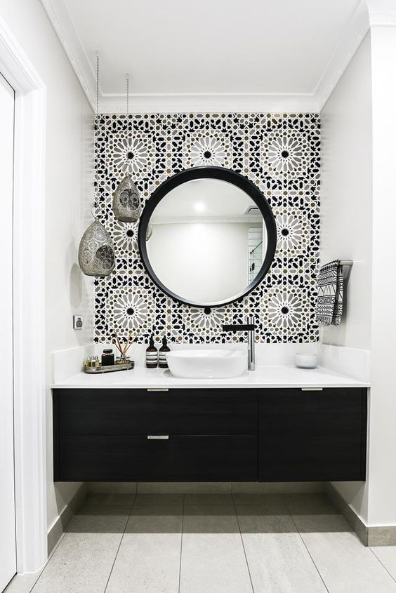 black and white bathroom with  round mirror