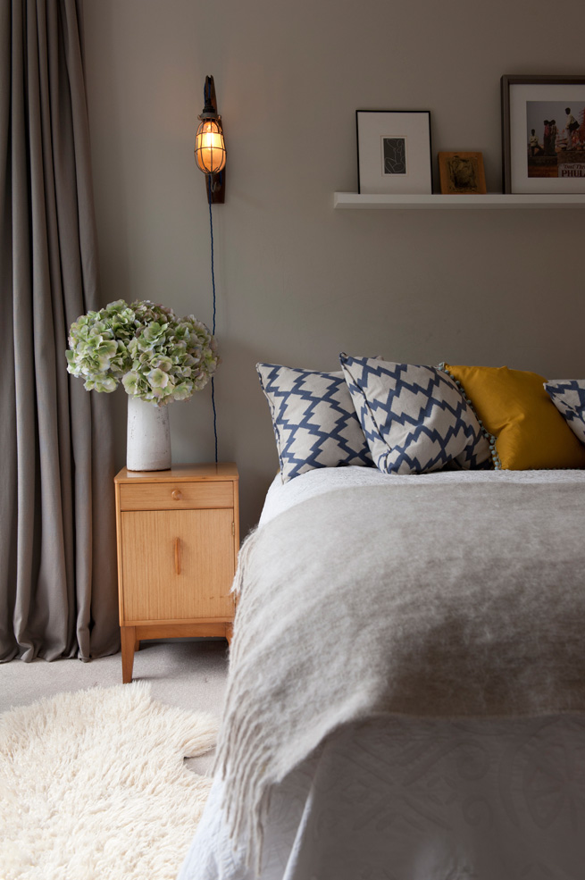 decorative pillows on bed with gray blanket
