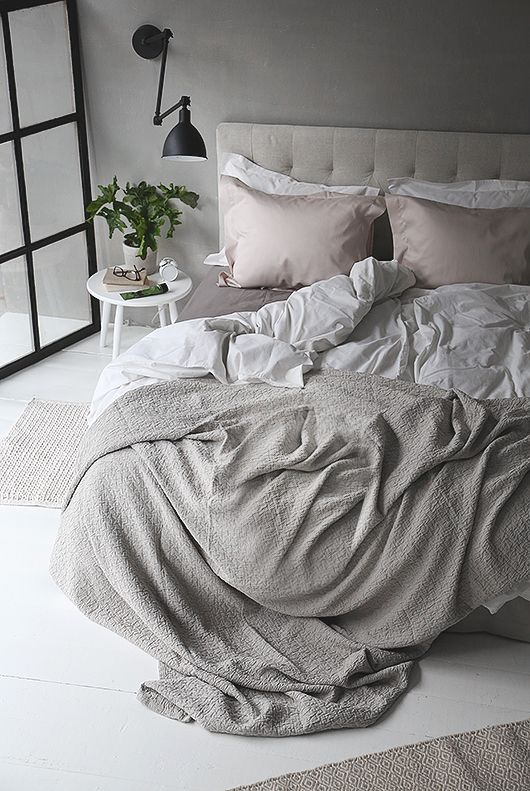 light grey room with pastel colored blankets