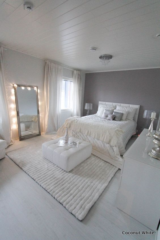 white bedroom with a big mirror with lights