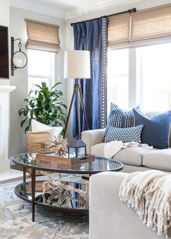 white sofas with blue pillows and curtains