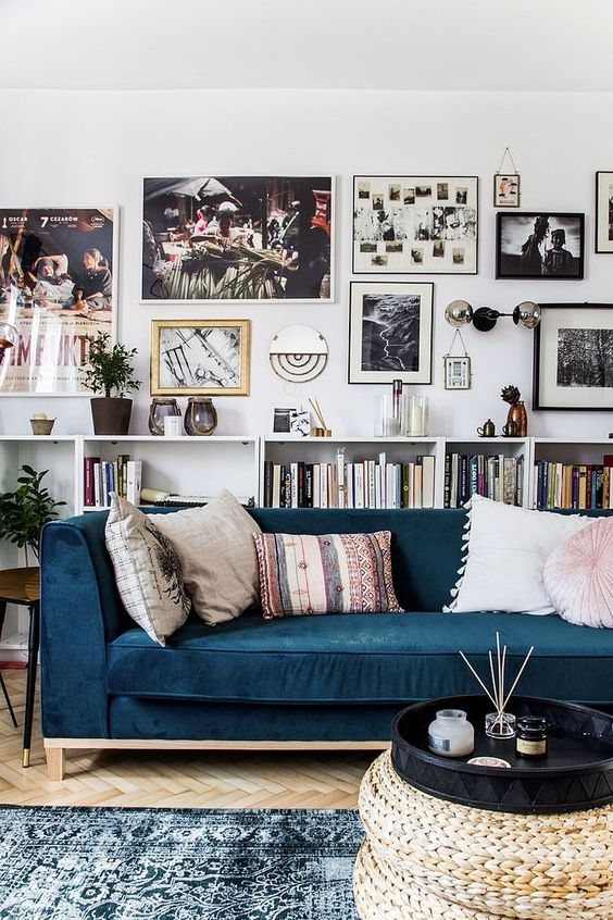 living room with blue velvet sofa and art wall gallery