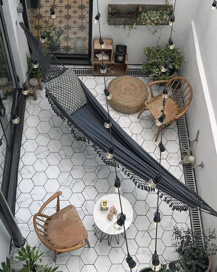 small patio apartment with white marble hexagon tiles grey hammock and lights decor