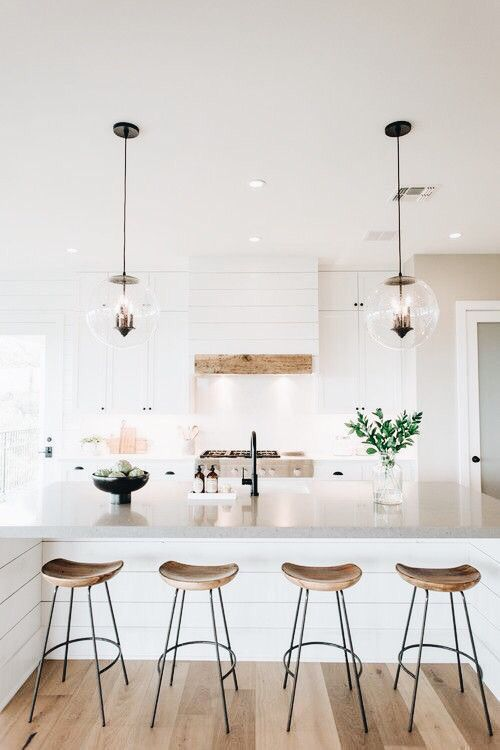 Open all-white kitchen with wooden stools