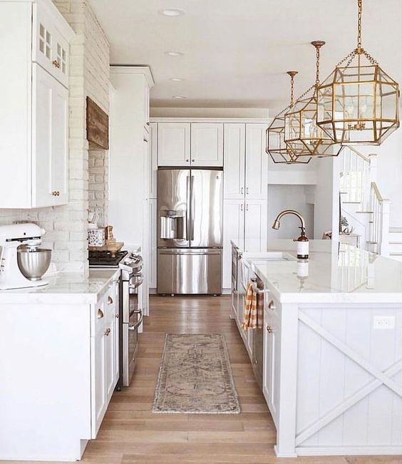 all white kitchen with white brick wall and brass/ gold accents