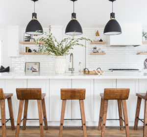 White Kitchen with black pendant lights, cognac leather bar stools, wood floors, open shelving