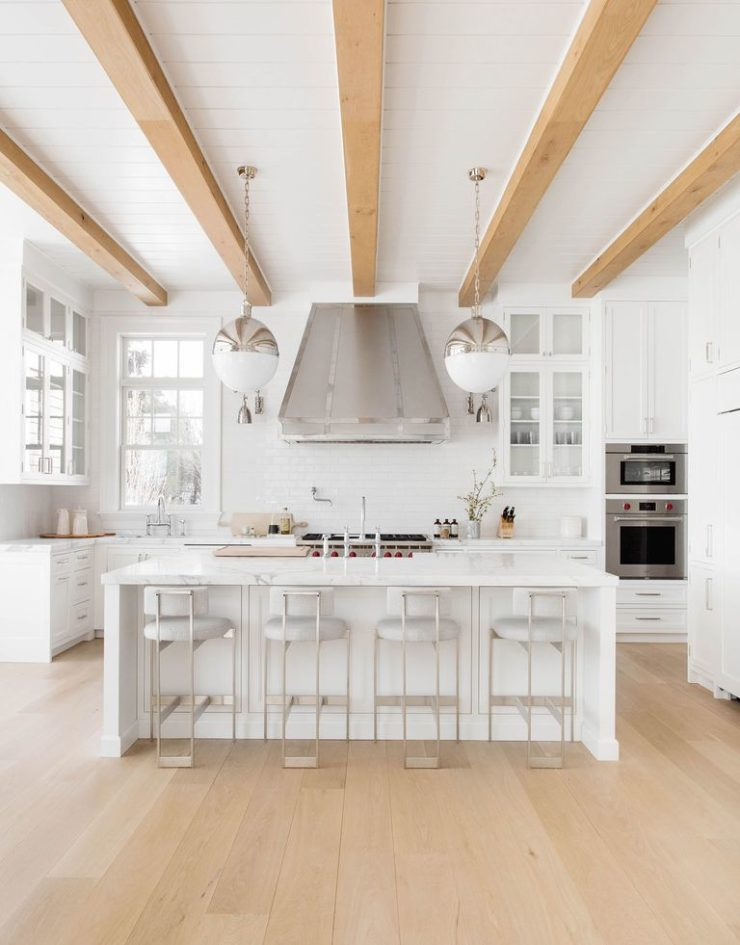 all white kitchen with exposed beams and wood floors