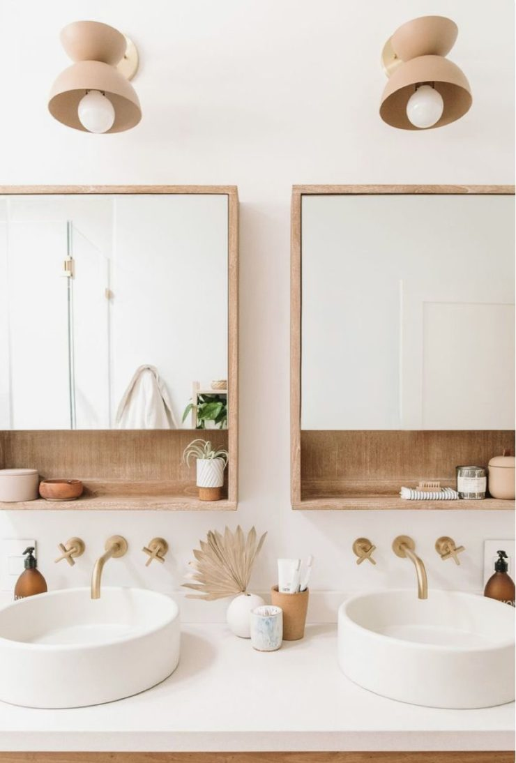 clear bathroom with double sink wood mirrors and gold faucets