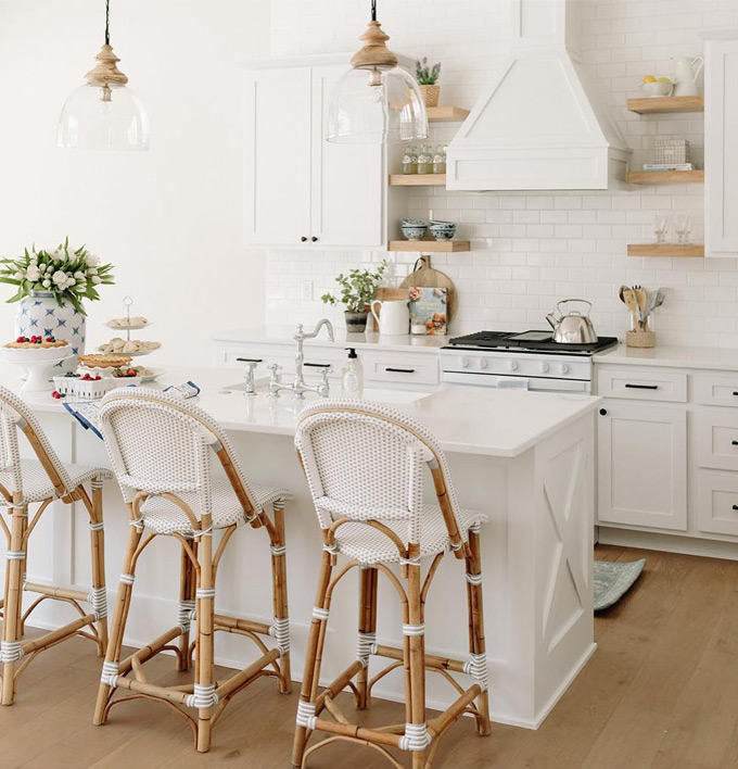 white kitchen with island french stools and wood open shelves
