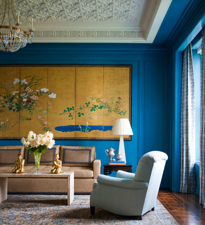 traditional living room with blue walls and large art above sofa
