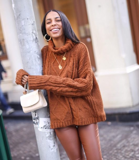 happy woman with brown Terracotta sweater with leather leggings